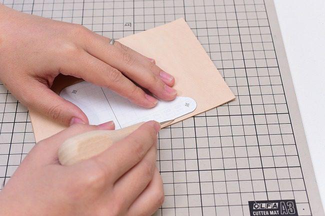 型紙がズレないようにしっかり押さえ、目打ちで型紙をなぞる