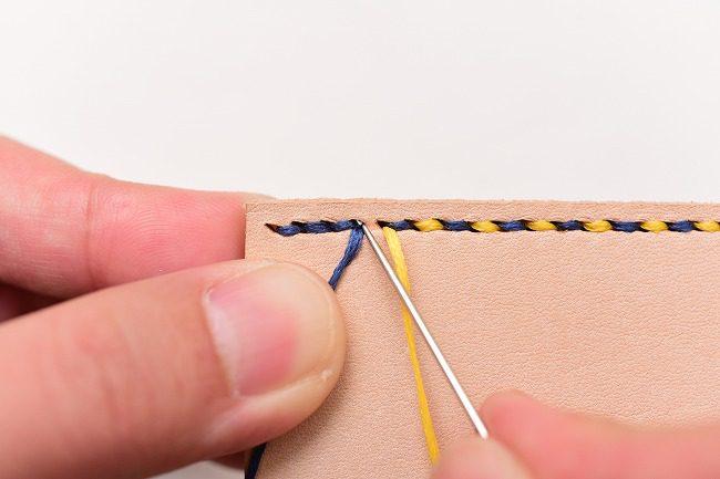 返し縫いで最後に通した青糸の穴に黄糸の針を通す