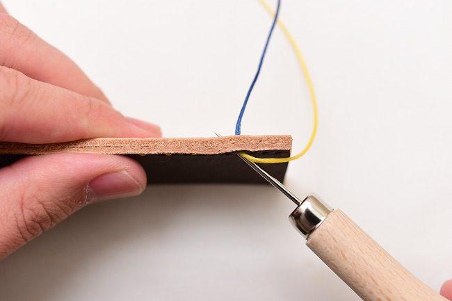 表に出た黄糸の穴へ、目打ちで斜めの穴をあける