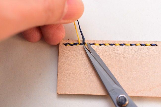 裏側から出た糸を根本でカットする