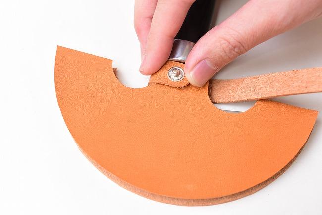 ナイフケースに留め具を巻き付け、ホックの穴位置を確認する
